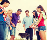 Group of friends making barbecue on the beach. Summer, holidays, vacation, happy people concept - group of friends having picnic and making barbecue on the beach royalty free stock photos