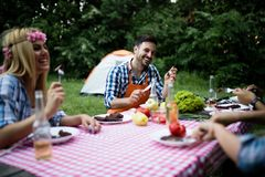 Group of friends making barbecue in the nature. Eating and sharing positive emotions stock photos