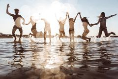 Group of friends making party on the beach at sunset time stock photography