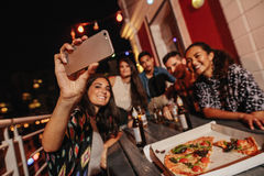 Group of friends making a selfie at rooftop party. Happy young people taking self portrait during party Royalty Free Stock Photo