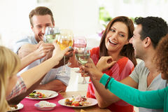 Group Of Friends Making Toast Around Table At Dinner Party. Holding Glass Of Wine Smiling Stock Photo
