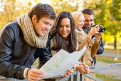 Group of friends with map and camera outdoors Royalty Free Stock Image
