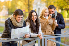 Group of friends with map and camera outdoors Royalty Free Stock Photography