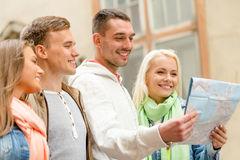 Group of friends with map exploring city Royalty Free Stock Images