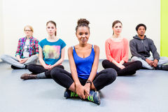Group of friends mediating doing yoga Royalty Free Stock Image