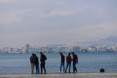 Group of friends meeting at seaside. In Konak - Izmir Turkey. At the other side of the sea gulf it is visible the other part of the city with high buildings royalty free stock images