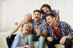 A group of friends with a microphone are singing fun songs indoo. A group of friends with a microphone are singing fun songs at a party indoors stock photo