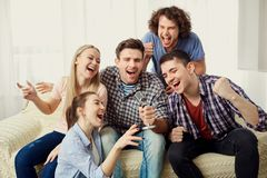 A group of friends with a microphone are singing fun songs indoo. A group of friends with a microphone are singing fun songs at a party indoors stock photos