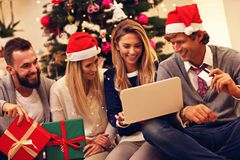 Group of friends ordering Christmas presents online Royalty Free Stock Photos