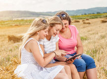 Group of friends outdoors with a tablet Royalty Free Stock Photos