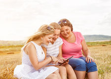 Group of friends outdoors with a tablet Royalty Free Stock Images