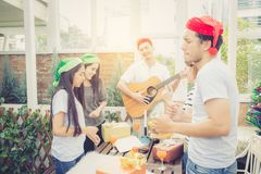 Group of friends party and playing guitar, Surprise birthday. Celebrate party christmas and new year, holiday and vacation concept Royalty Free Stock Image