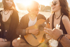 Group of friends partying and listening to music. At sunset Royalty Free Stock Photos