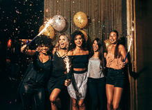 Group of friends partying in nightclub. Shot of group of young women celebrating new years eve at the pub. Group of female friends with sparklers partying in Royalty Free Stock Photography