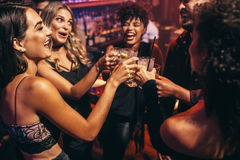 Group of friends partying in a nightclub. And toasting drinks. Happy young people with cocktails at pub Royalty Free Stock Image