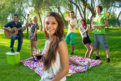 Group of friends partying in the park. Group of young college friends partying in the park with a pretty young teenage girl in the foreground smiling at the royalty free stock photo