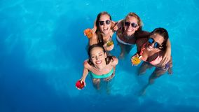 Group of friends partying in pool stock photo