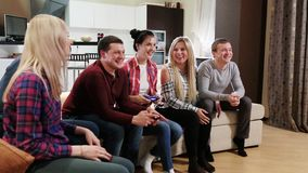 Group of friends people enjoy relaxing on couch playing videogames. Friends playing video games while laughing in the living room stock video