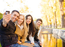 Group of friends with photo camera in autumn park stock images