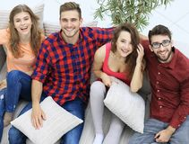 Group of friends with pillows, sitting on the couch Royalty Free Stock Photos