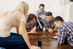 A group of friends play board games on the floor indoors. A group of friends play board games on the floor having fun at a party indoors Stock Photo