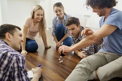 A group of friends play board games on the floor indoors. A group of friends play board games on the floor having fun at a party indoors Royalty Free Stock Photography