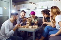 A group of friends play board games in the room. A cheerful group of friends play board games in the room royalty free stock photos