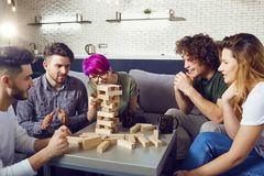 A group of friends play board games in the room. A cheerful group of friends play board games in the room Stock Photography