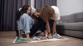 A group of friends play in games on the floor indoors. Young people having fun together at home in loft interior room stock video