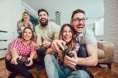 Group of friends play video games together. Group of friends play video games together having fun Stock Photo