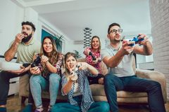Group of friends play video games together at home. Having fun Stock Images