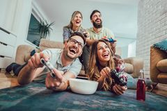 Group of friends play video games together at home. Having fun Stock Photos