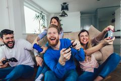 Friends play video games together at home, having fun stock images