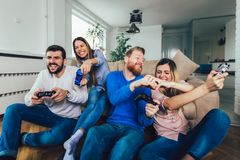 Friends play video games together at home, having fun royalty free stock image