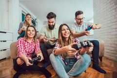 Group of friends play video games together. At home, having fun Royalty Free Stock Photography