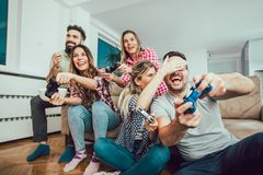 Group of friends play video games together at home. Having fun Royalty Free Stock Images