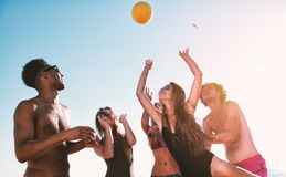 Group of friends playing at beach volley at the beach stock image