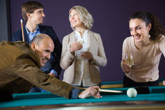 Group of friends playing billiards and smiling in billiard room Royalty Free Stock Photos