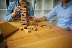 Group of Friends playing blocks wood game on the table folded pu Royalty Free Stock Photography