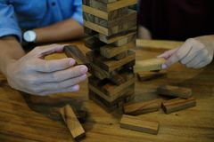 Group of Friends playing blocks wood game on the table folded pu Royalty Free Stock Image