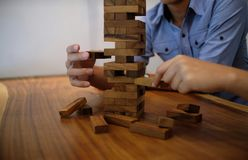 Group of Friends playing blocks wood game on the table folded pu Stock Image