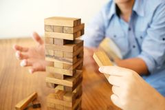 Group of Friends playing blocks wood game on the table folded pu Stock Photo