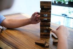 Group of Friends playing blocks wood game on the table folded pu Royalty Free Stock Images