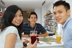 A group of friends playing a board game. A group of friend playing a board game at a cafe Royalty Free Stock Photo