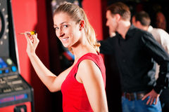 Group of friends playing darts royalty free stock photography