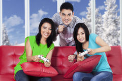 Group of friends playing games on sofa Royalty Free Stock Photo