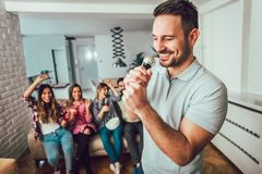 Group of friends playing karaoke at home. Concept about friendship, home entertainment and people stock photo