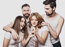 Group of friends playing karaoke over white background. Concept about friendship and people. Studio shoot Stock Image