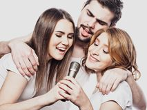 Group of friends playing karaoke over white background. Concept about friendship and people. Studio shoot Royalty Free Stock Images