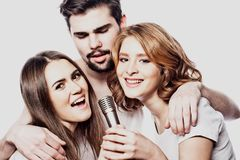 Group of friends playing karaoke over white background. Concept about friendship and people. Studio shoot Royalty Free Stock Photos
